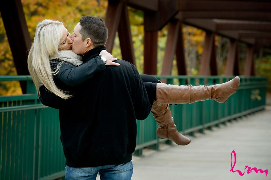Stunning photo of engaged couple kissing on a bridge in London Ontario