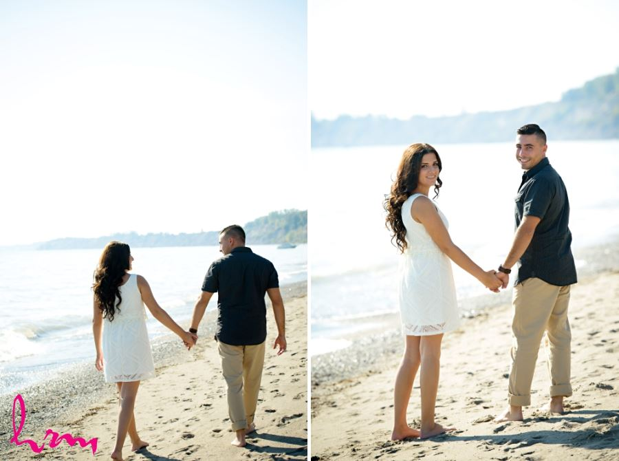 sunny beach engagement session couple walking on sand