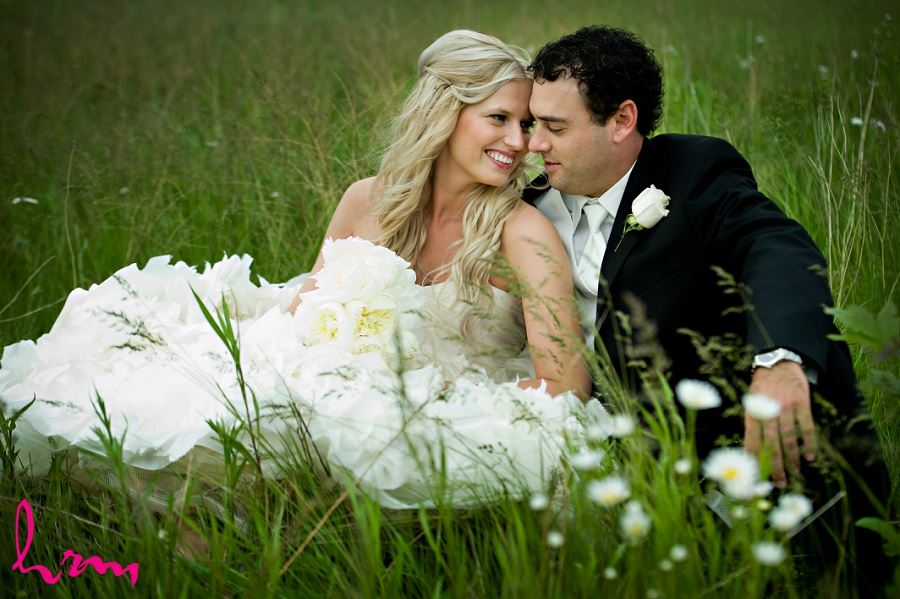 Wedding photo of bride and groom sitting in grass