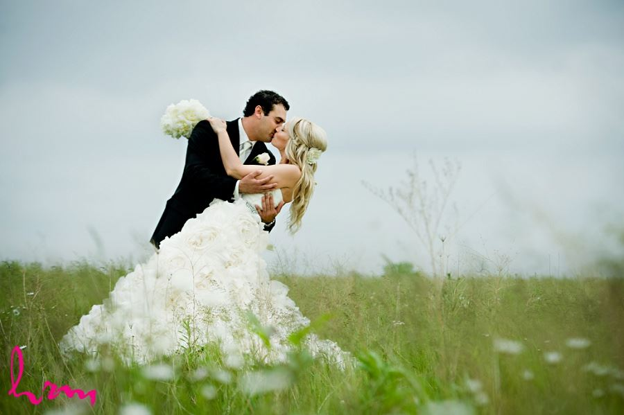 Wedding photo of bride and groom kissing in a field