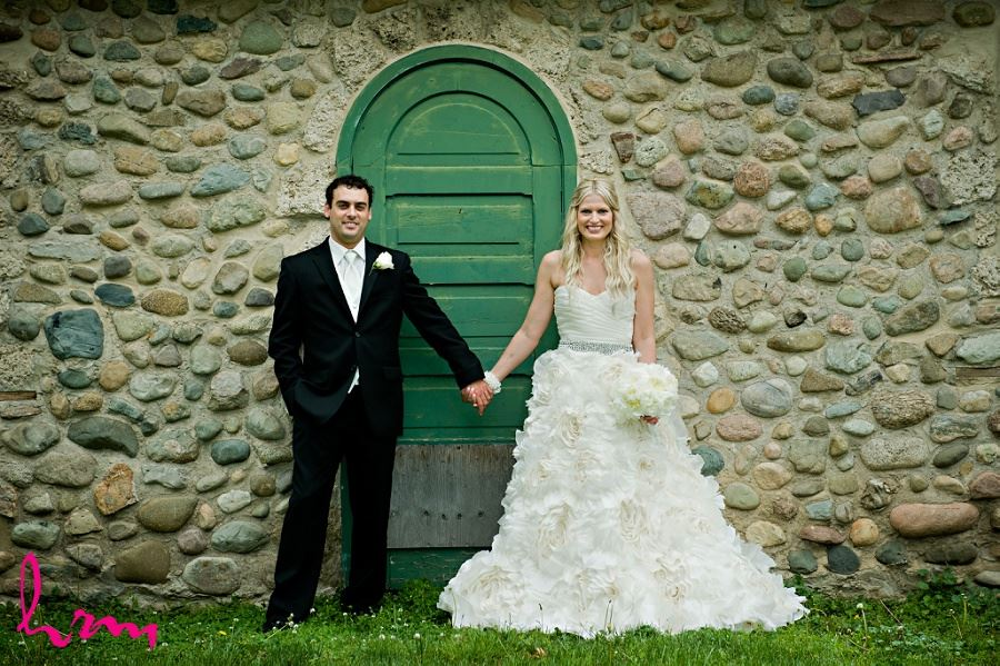Wedding photograph of bride and groom in front of stone wall