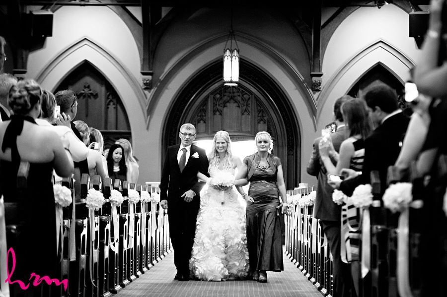 black and white wedding photo of bride walking down aisle with parents