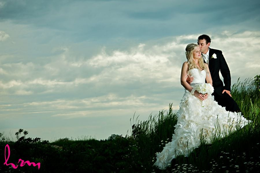Photo of Ania and Ken on grass hill taken by London Ontario wedding photographer