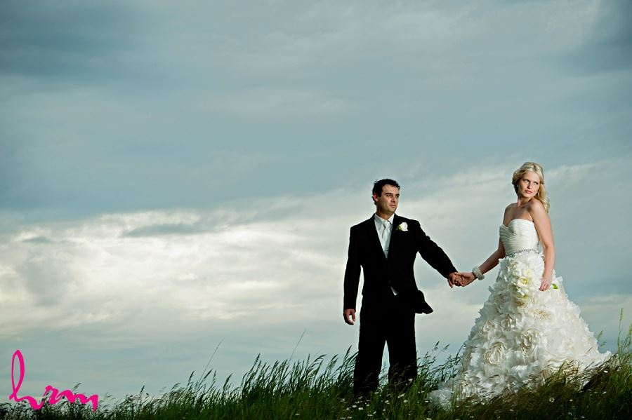 Photo of bride and groom grass hill taken by London Ontario wedding photographer