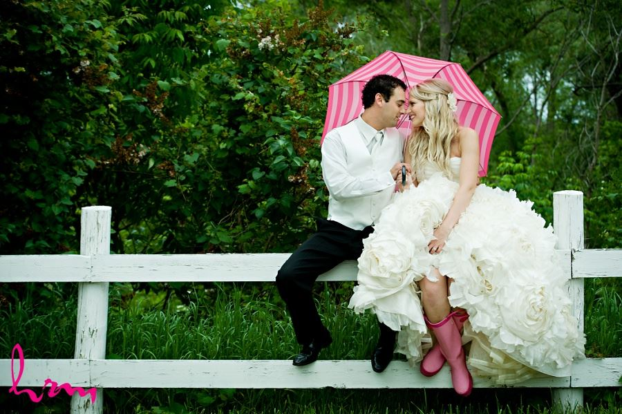 Wedding photo of bride and groom sitting on fence