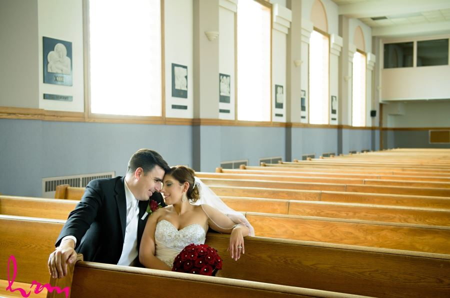 bride and groom sitting in pews of church
