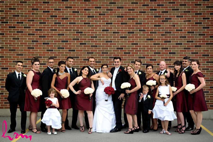 wedding party in front of brick wall