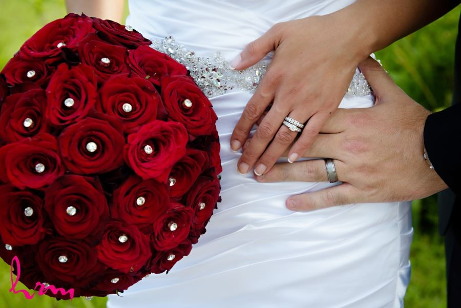 bride and grooms hands with rings and bouquet