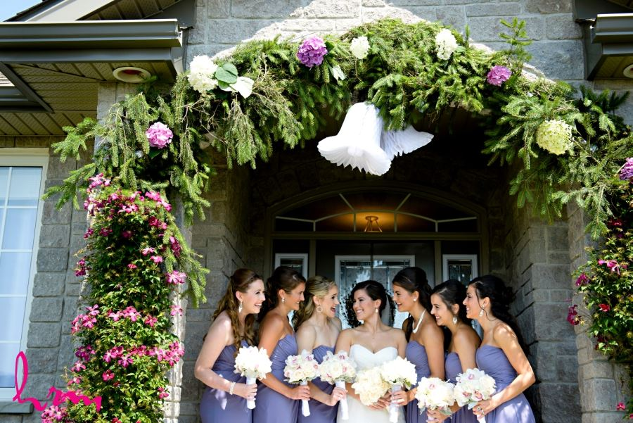 floral and evergreen arch over door wedding day