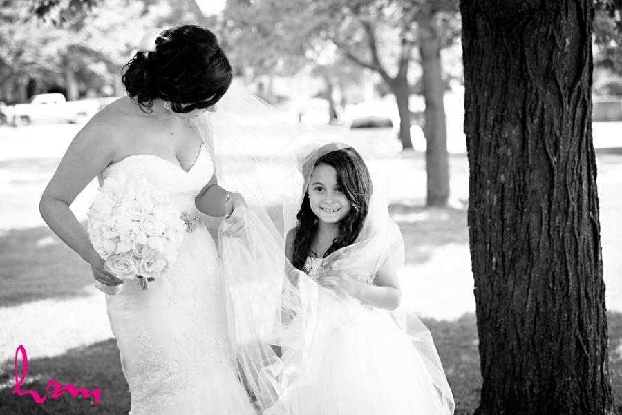 junior bridesmaid with bride under veil