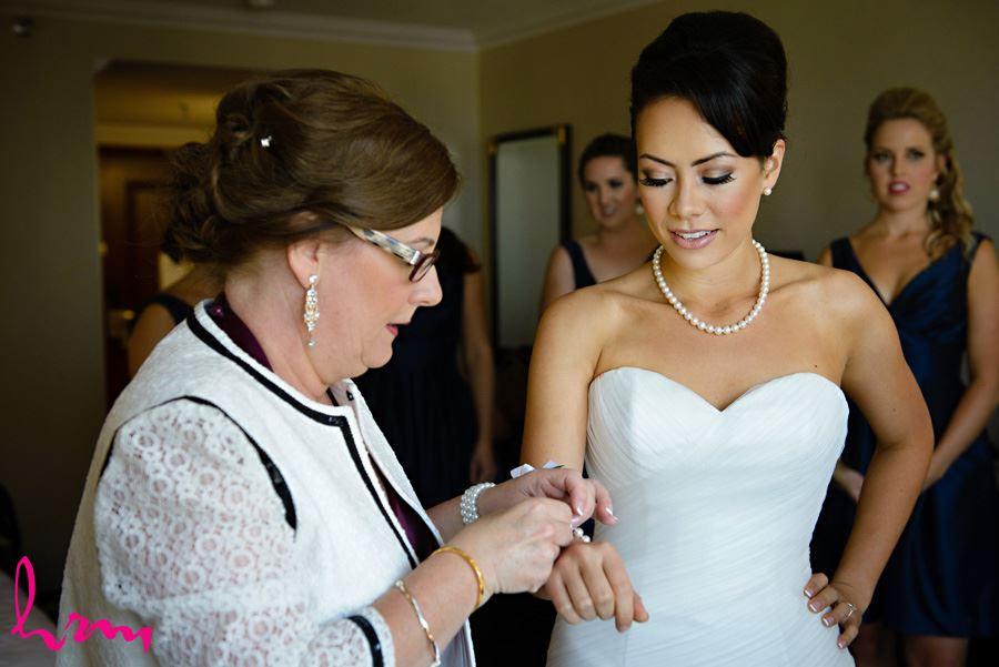 Geneviève putting on bracelet London ON Wedding Photography