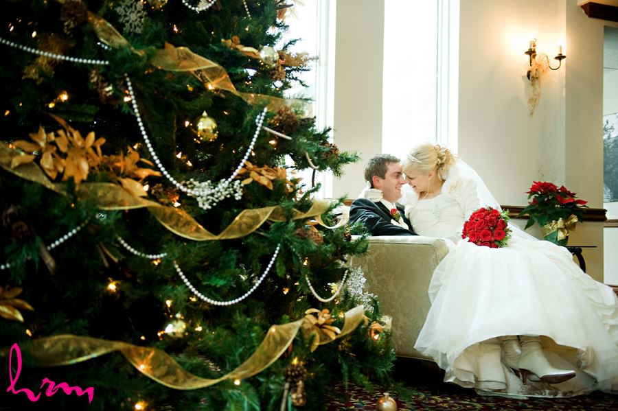 bride and groom sitting by christmas tree