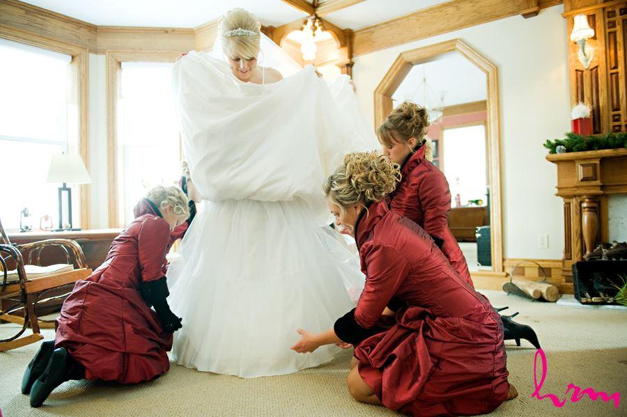 bridemaids helping bride get dressed at brides house