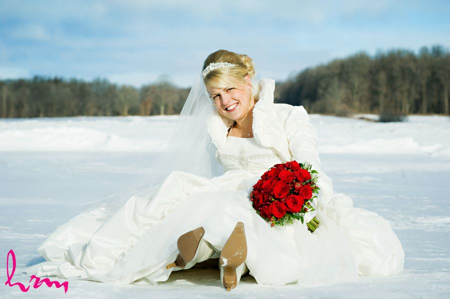 winter bride sitting in the snow with red roses