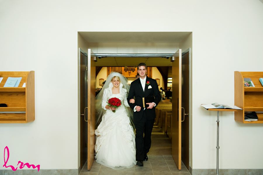 bride and groom walking out of church after getting married