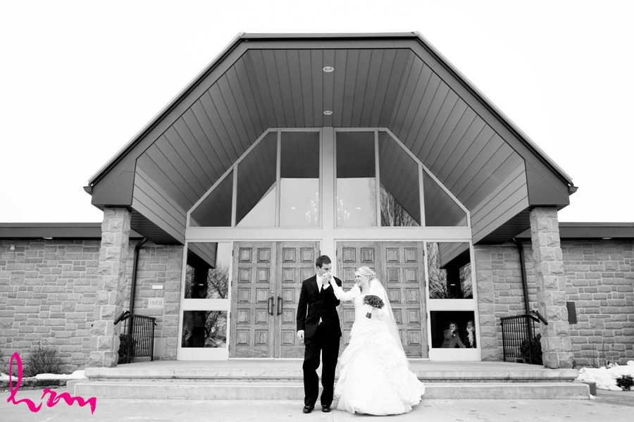 winter bride and groom outside church after getting married