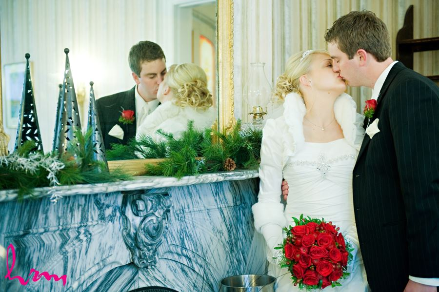 bride and groom kissing by a mirror