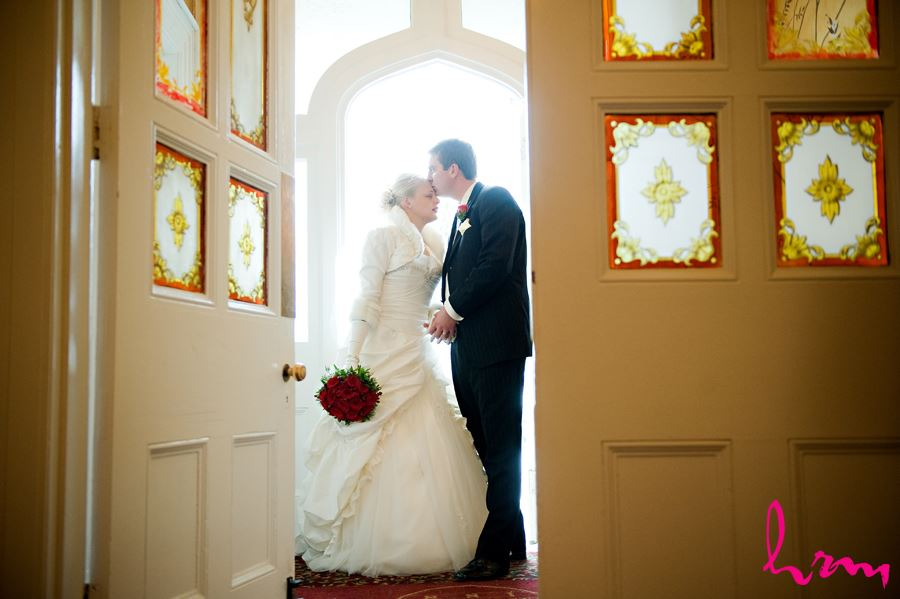 bride and groom sharing a kiss by a doorway at the elmhurst inn in ingersoll