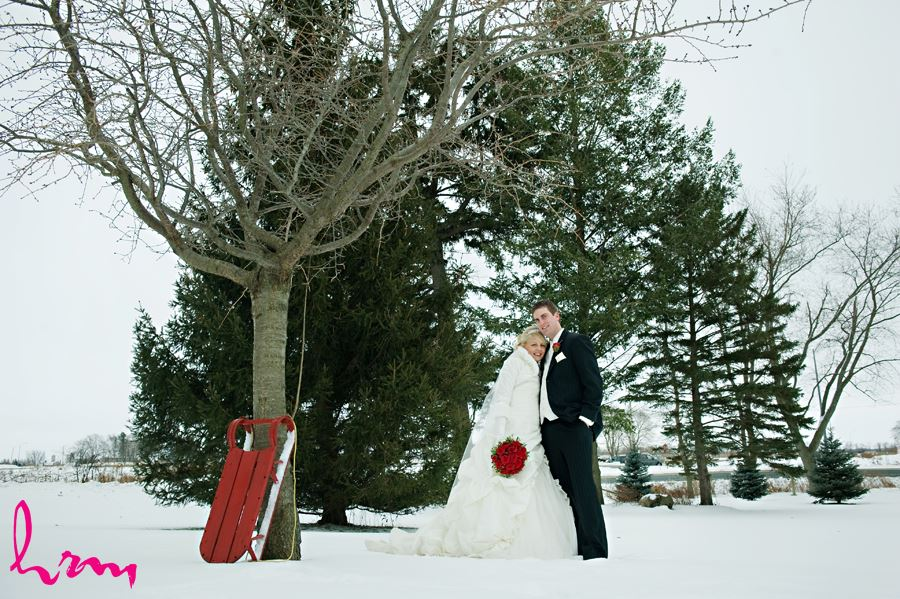 bride and groom by a tree in the snow with a sled
