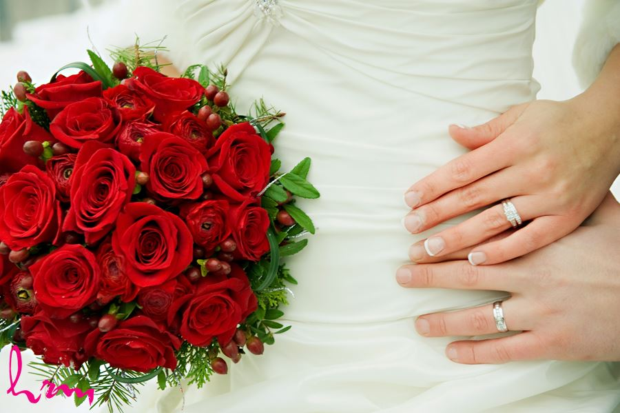 wedding rings close up with red roses