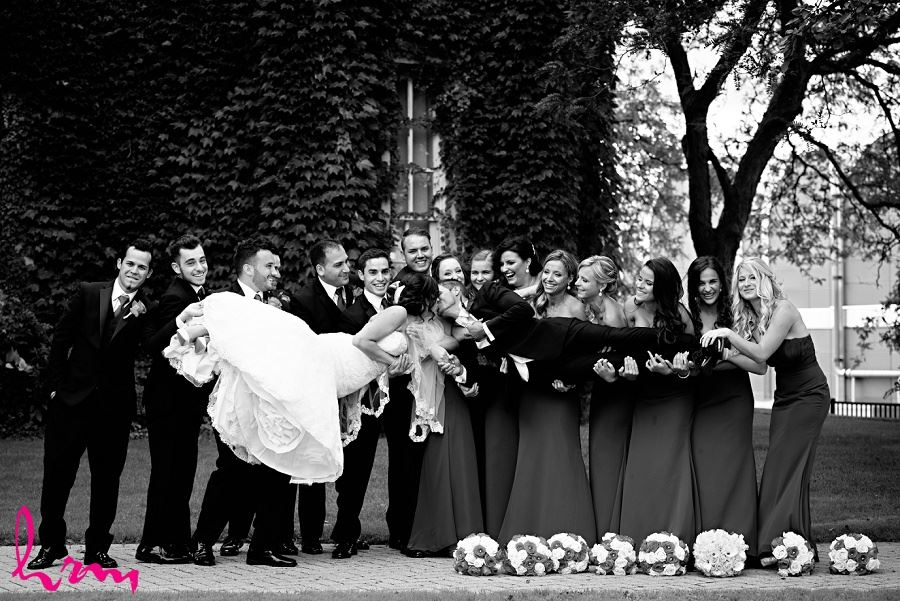 fun wedding day photo idea with wedding party and bride and groom kissing