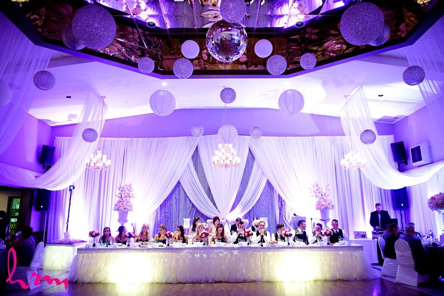 head table with draping and sequinned backdrop and chandeliers