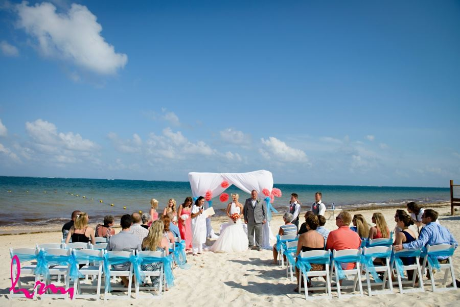 Beach wedding ceremony with pompoms and chair decor
