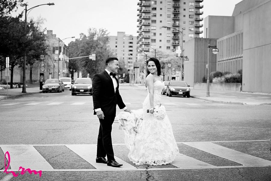 Lauren + Jose crossing street in downtown London ON Wedding Photography