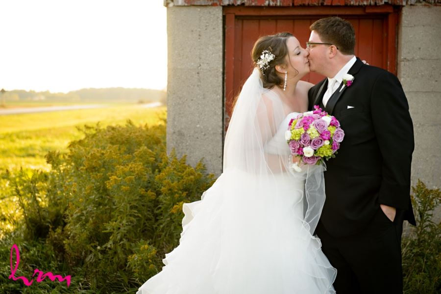 bride and groom kissing in field with barn