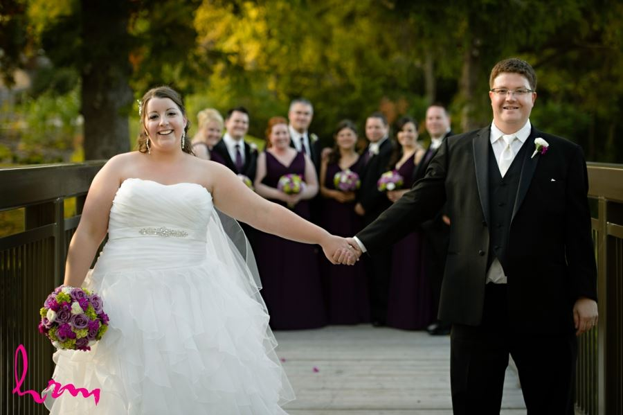 bride and groom holding hands in front of wedding party
