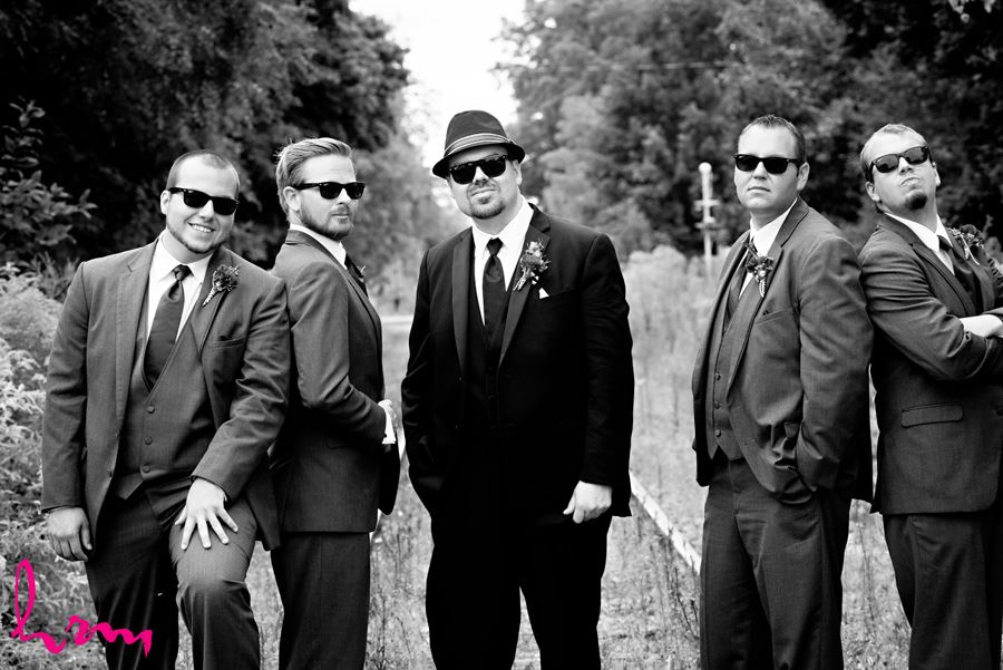 Black and white photo of Will and groomsment outside CASO Railway Station St. Thomas ON Wedding Photography