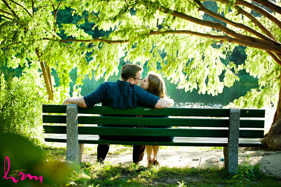 Engaged couple cuddling on a bench near the lake