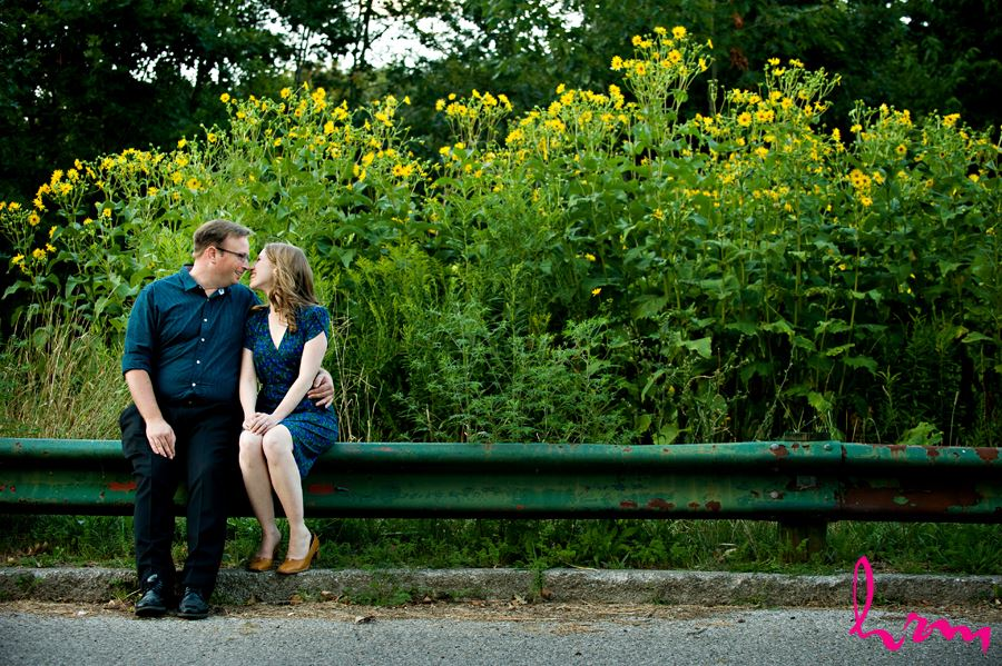 Beautiful engaged couple sitting on railing with yellow flowers behind them