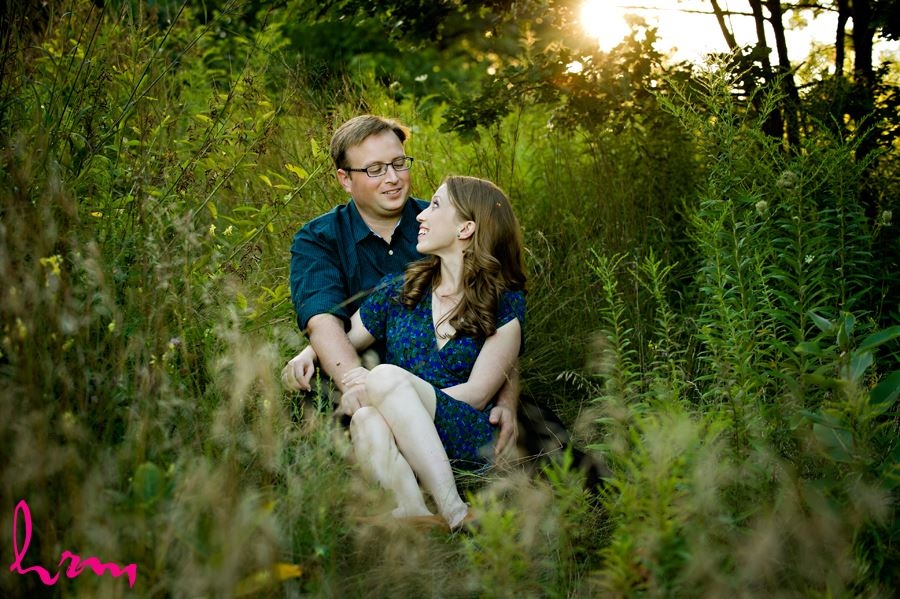 Engaged couple cuddling in grass at sunset