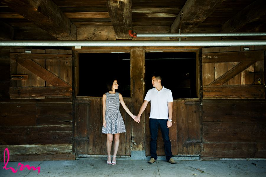 Engaged couple infront of wooden barn doors at Riverdale Farm