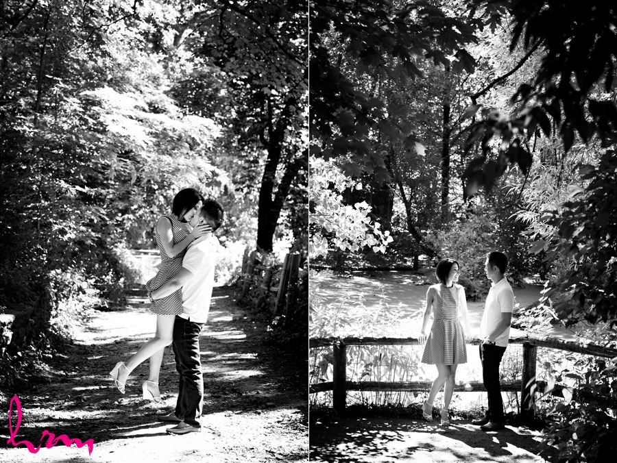 Engaged couple kissing in forest near river in black and white