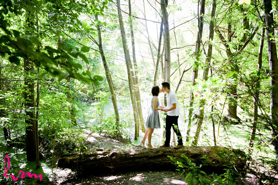 Engaged couple sneaking a kiss in the middle of the forest