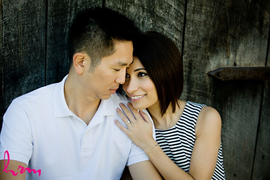 Engaged couple cuddling in front of wooden structure