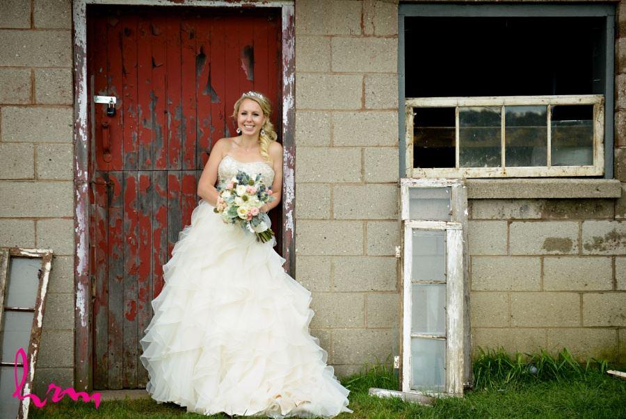 Bride in front of old red barn door