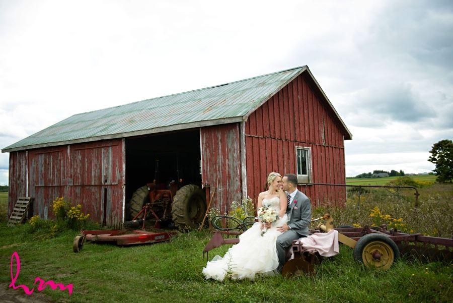 Bride and groom in front of old red barn farm wedding
