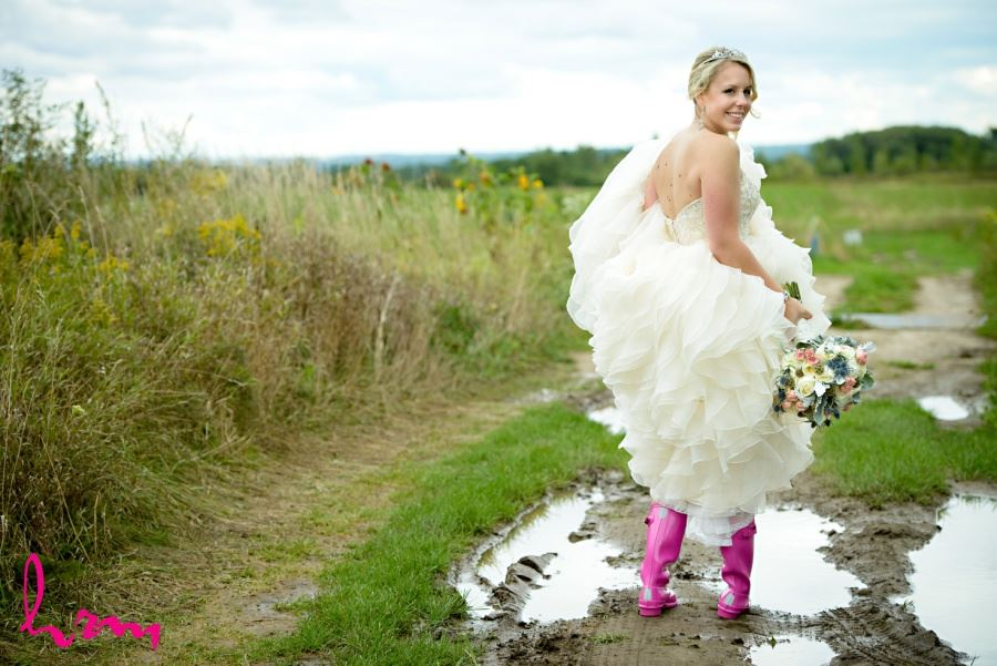 Bride in hot pink galloshes rain boots in puddle on wedding day