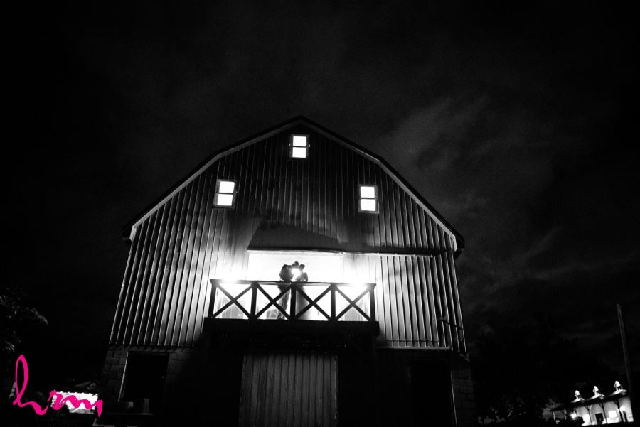 Bride and Groom in front of barn nighttime kissing shot