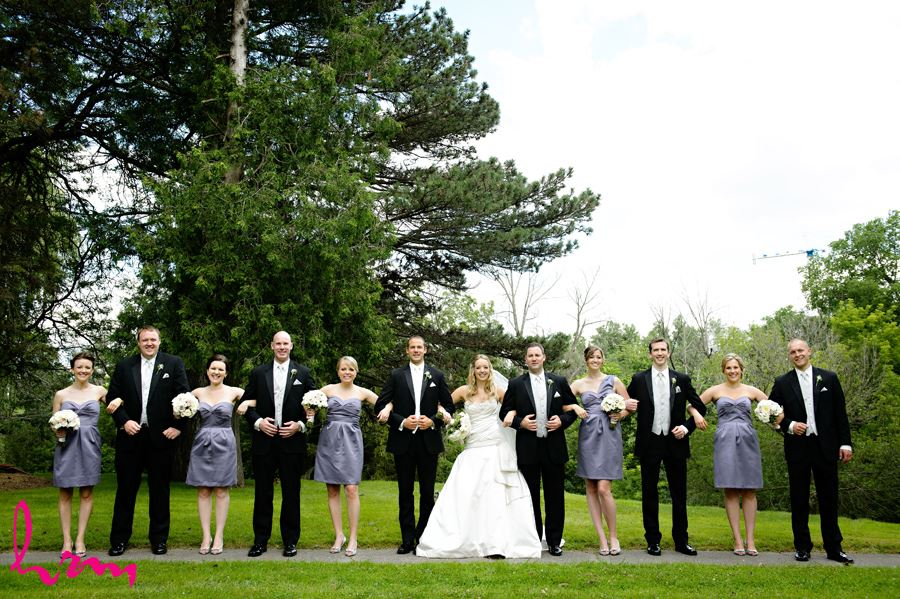 Unique photo of wedding party all linking arms wearing purple in London Ontario