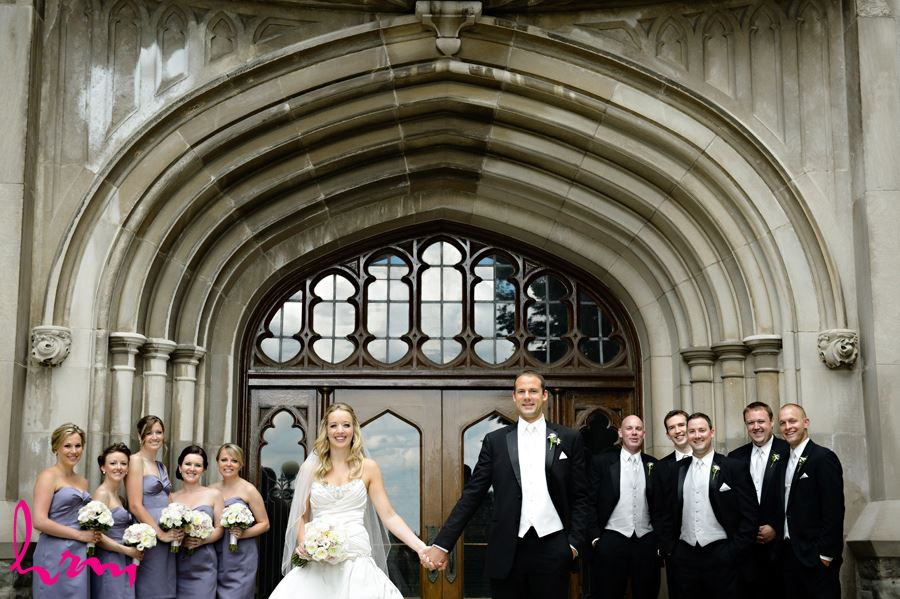 Bride and Groom with their bridal party in front of arch doorway infront of University College at Western University