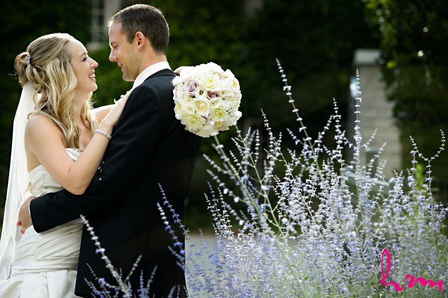 Smiling bride and groom with blue flowers in foreground at Western University