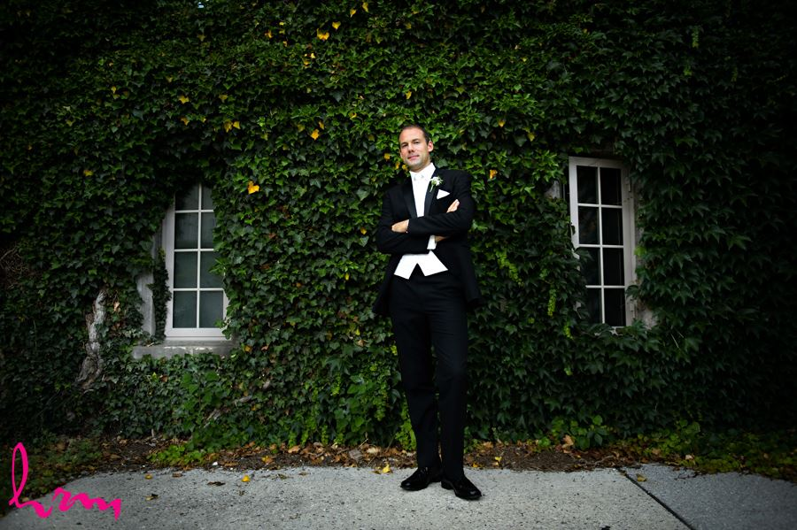 Groom standing in front of wall filled with green leaves at Western University