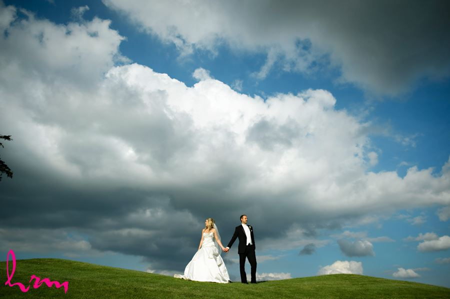 Bride and groom pose on a green hill with bright blue sky andbig white clouds