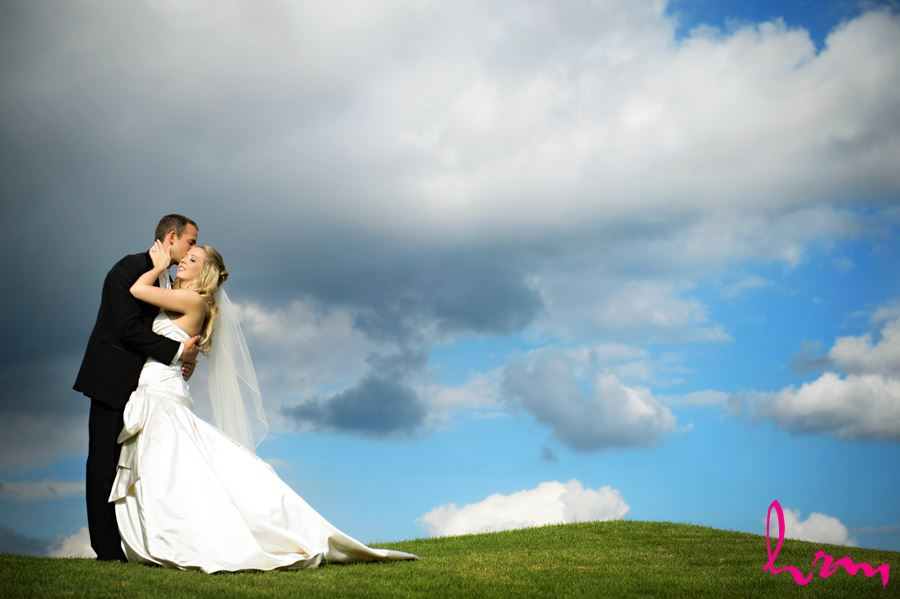 Groom kissing brides forehead on a green hill with bright blue background and big white clouds in London Ontario