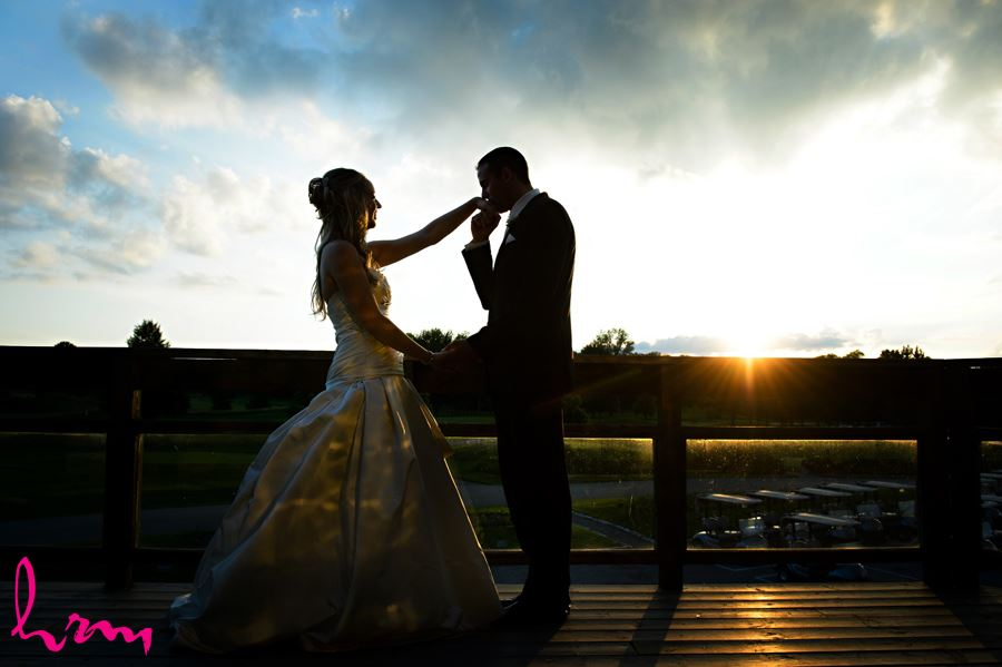 Groom kissing bride at sunset at West Haven Golf