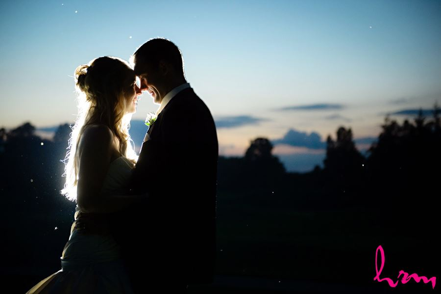 bride and groom cuddle forehead to forehead at night in London Ontario